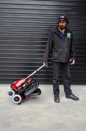 Mobie Portable Scooter - folded and wheeled by tiller
