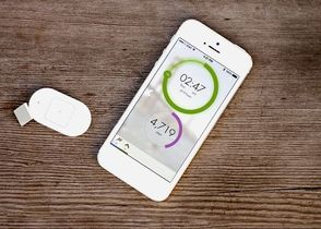 Lumo Lift device next to smart phone with app installed